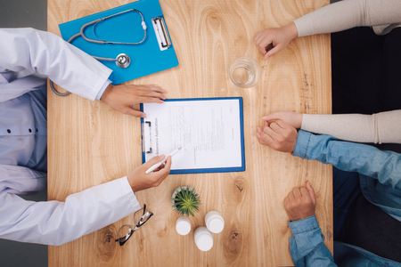 Doctor writing down medical records and talking with a couple during a visit, desktop top view, unrecognizable people