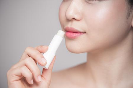 회색 배경 위에 위생 입술 연고를 적용 아시아 여자