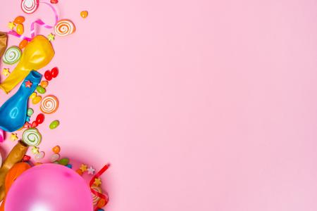 セレブレーションフラットレイ。ピンクの背景にカラフルなパーティーアイテムとキャンディー。 写真素材