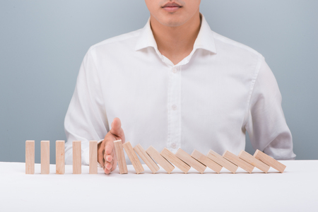 Hand of businessman stop dominoes continuous toppled