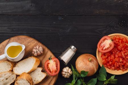 Voorbereiding van heerlijke Italiaanse tomatenbruschetta met gehakte groenten, kruiden en olie Stockfoto