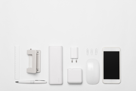White office supplies  and smartphone on white table background with copy space. 免版税图像