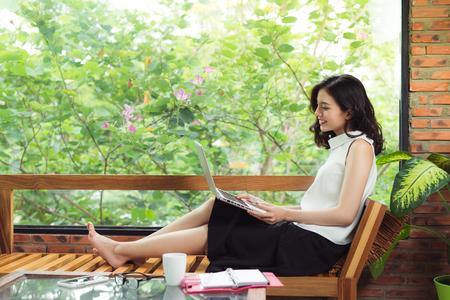 創造的なオフィスやカフェの窓のそばに座ってラップトップを持つアジア女性