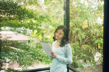 Young attractive sweet girl with notepad on a veranda. Spring mood. Stock Photo