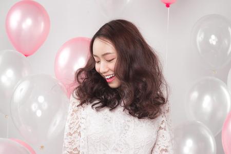 Aziatische vrij modieuze vrouw in witte jurk met pastel ballonnen Stockfoto