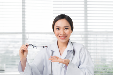 Female oculist giving a pair of eyeglasses