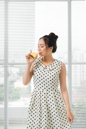 Young attractive asian woman drinking hot tea at home