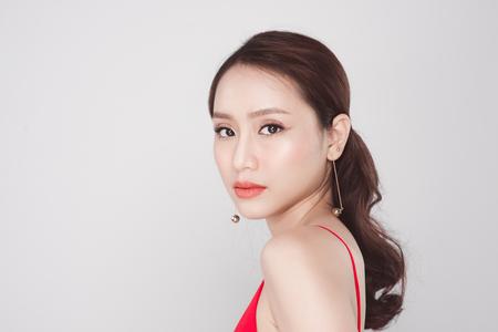 Portret van modieuze Aziatische vrouw die rode kleding op grijze achtergrond draagt.