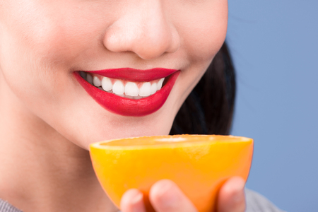 Healthy food. Close-up of dmiling lovely pinup asian girl holding orange over blue background. Banque d'images