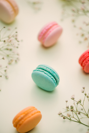 Morning cake macaron and flower gypsophila on light green background from above. Cozy breakfast. Flat lay style.