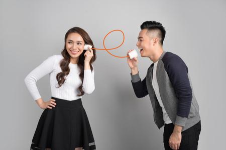 회색 배경에 고립 된 수있는 전화로 젊은 아시아 부부
