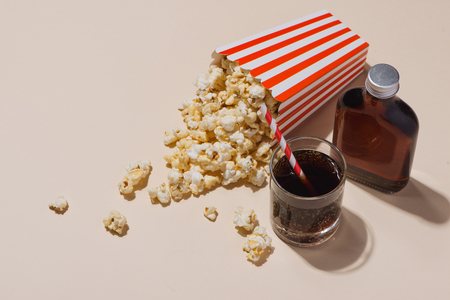 Popcorn in red and white cardboard with glass of soda Banco de Imagens