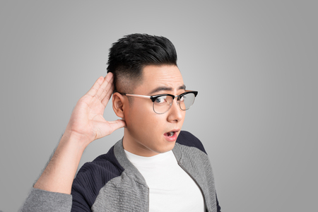 Businessman with hand behind ear listening closely against gray background