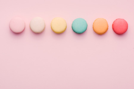 Top view of mini pink and white macaron on soft sweet pink paper background 写真素材