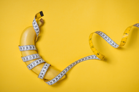 Measuring tape wrapped around a banana isolated on a yellow background, Concept of diet. Reklamní fotografie