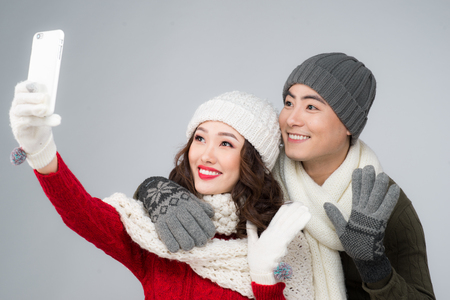 Happy young hipster couple hugging. Cold season. Taking selfie photo Stock Photo