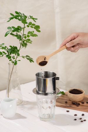 Coffee dripping in vietnamese style on wooden table Banco de Imagens