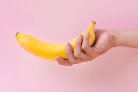 a man holding a banana isolated on pink background