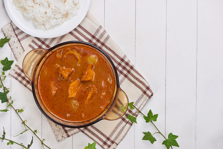 Chicken curry with spice on wooden background