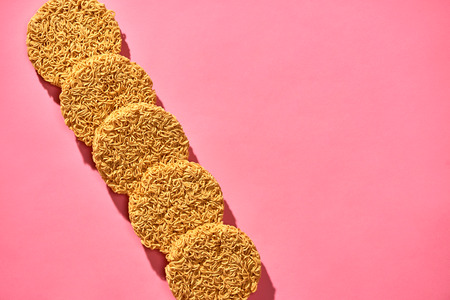 Dried instant noodles isolated on a pink background