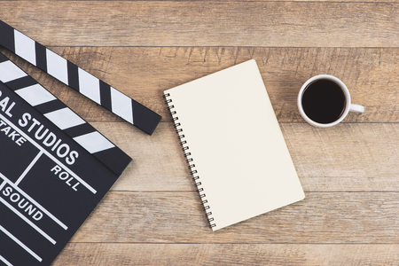 木製のテーブルの上の映画のクラッパーとメモ帳。トップビュー。 写真素材