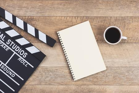 Filmklep en blocnote op de houten lijst. Bovenaanzicht Stockfoto