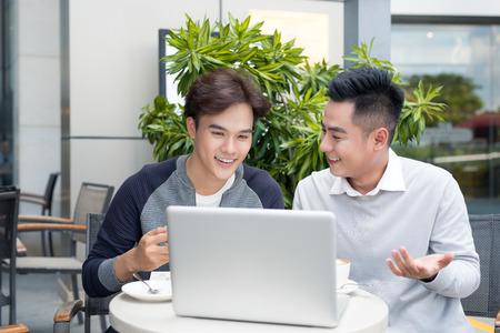 Twee zakenlieden die terwijl het hebben van een vergadering in een klassiek koffiewinkelterras lachen, die een laptop computer met behulp van.