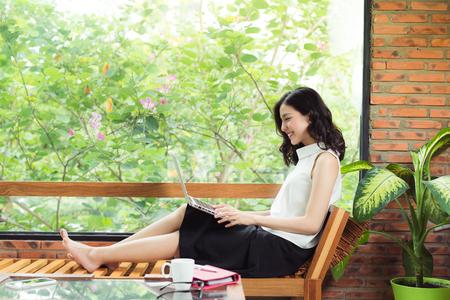 クリエイティブオフィスやカフェの窓の近くにノートパソコンを持つアジアの女性 写真素材