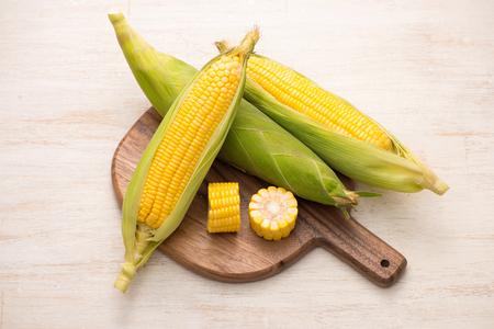 Suikermaïs op maïskolven op scherpe raad op houten lijst.