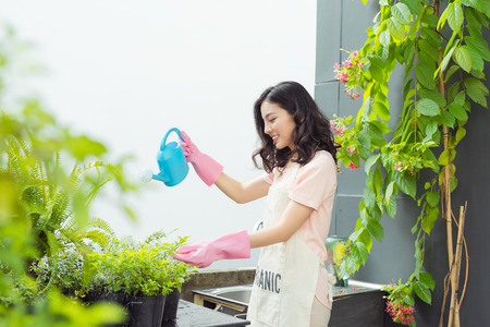 Beautiful asian woman gardener watering the plants