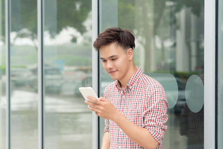 Asian man use of the cellphone standing outdoors