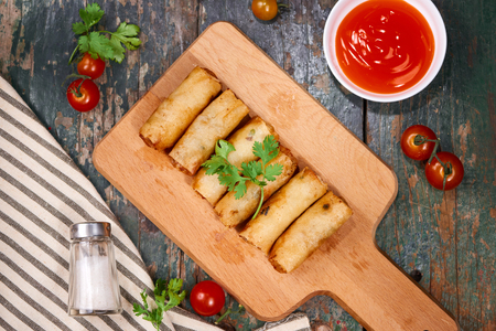 Vietnamese food. Delicious homemade spring rolls on wooden table. Stock Photo