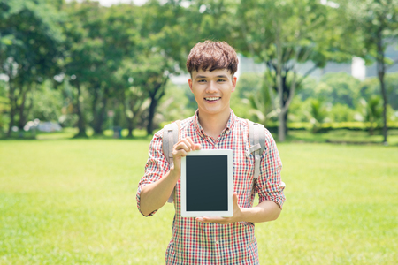 Cheerful young man in checkered shirt pointing on blank screen tablet outdoors Stock Photo