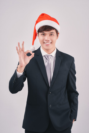Asian businessman celebrating christmas making the ok thumbs up sign