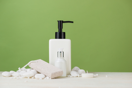 SPA Decoration. Spa composition with cosmetic bottle over green. Stock Photo