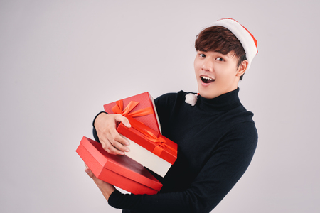 Asian man offering a christmas gift isolated on white background