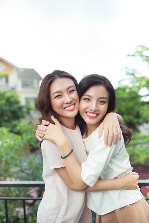 Felices mujeres jóvenes amigos bien vestidos sonriendo mientras está de pie juntos