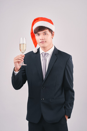 Attractive young santa businessman holding champagne glass