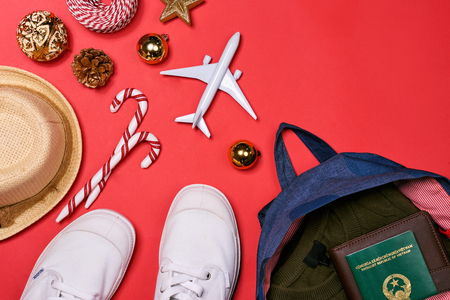 Preparation for travel concept - passport, camera, hat, airplane, chrismas decorations on red background