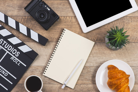 Office things with movie clapper, digital table, coffee cup, pen and notepad on the wood table 版權商用圖片