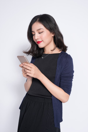 Portrait of a smiling asian casual woman holding smartphone over white background