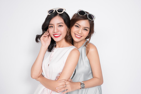Two beautiful young women  hugging and looking to camera.