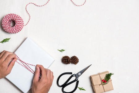 Male hands wrapping xmas gifts. Packages wrapped in kraft paper tied with jute Reklamní fotografie