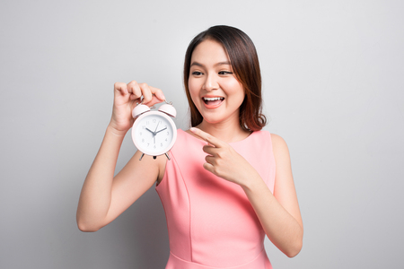 Surprised woman holding an alarm clock in her hand and looking at it with opened mouth  Stock Photo