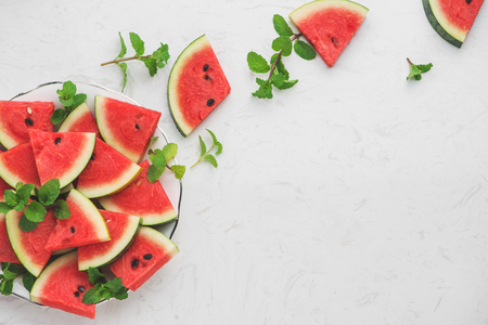 Watermelon slices, green mint leaves on white background. Top view, flat lay. Stockfoto