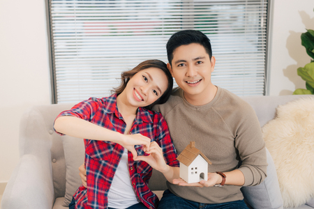 Happy smiling couple holding a model house. Home insurance concept 스톡 콘텐츠