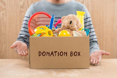Mannelijke vrijwilligersholding schenkingsdoos met oud speelgoed. Stockfoto