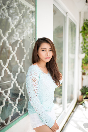 Young asian woman relaxing on a balcony  enjoying fresh air.