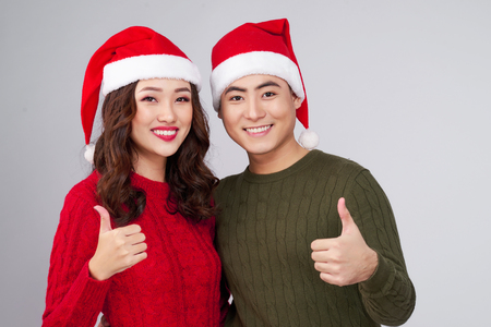Asian couple wearing christmas hat gesture hands. Stock Photo