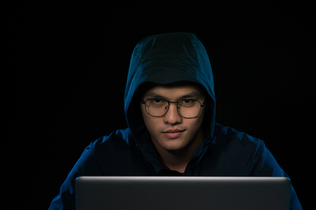 Asian hacker hacking computer network with laptop in dark. Cyber security concept Stock Photo